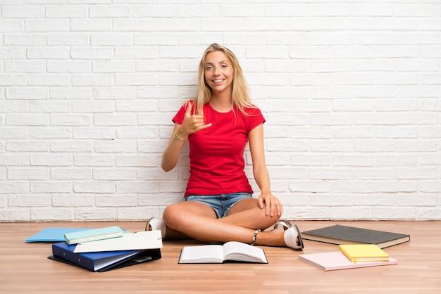 電話ジェスチャーを作る床の上の多くの本を持つ若い金髪学生少女