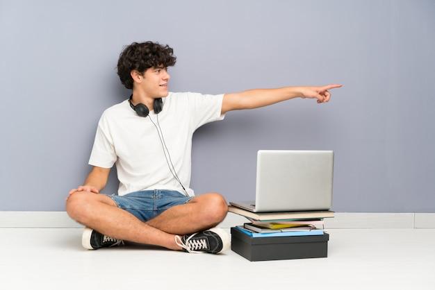 彼のラップトップを座っている若い男