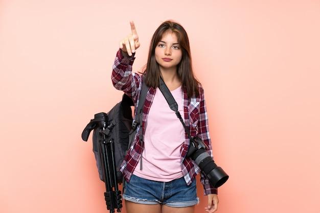 透明なスクリーンに触れる若い写真家の女の子