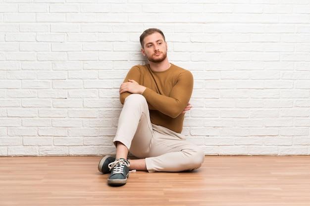 アイデアを考えて床に座っている金髪の男