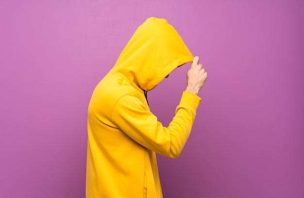 黄色のスウェットシャツを持つハンサムな男