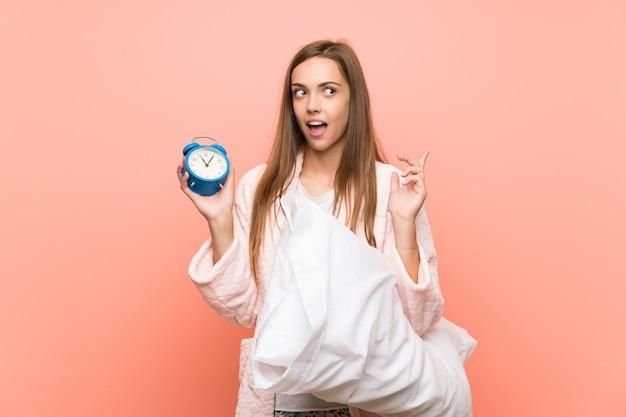 ビンテージ時計を保持しているピンクの壁の上のドレッシングガウンの若い女性