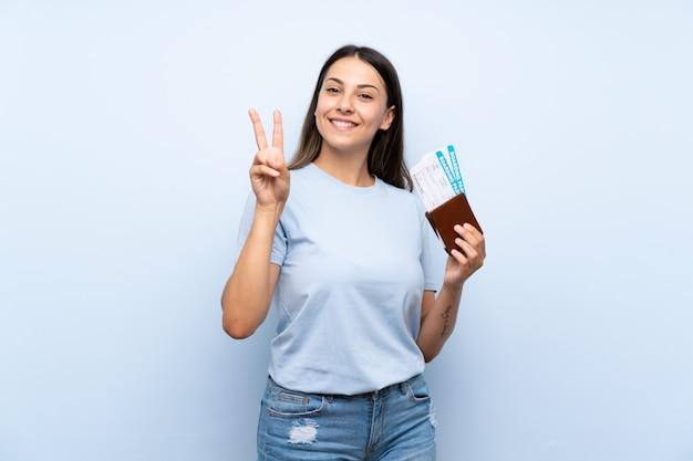 Женщина путешественника с посадочным талоном усмехаясь и показывая знак победы