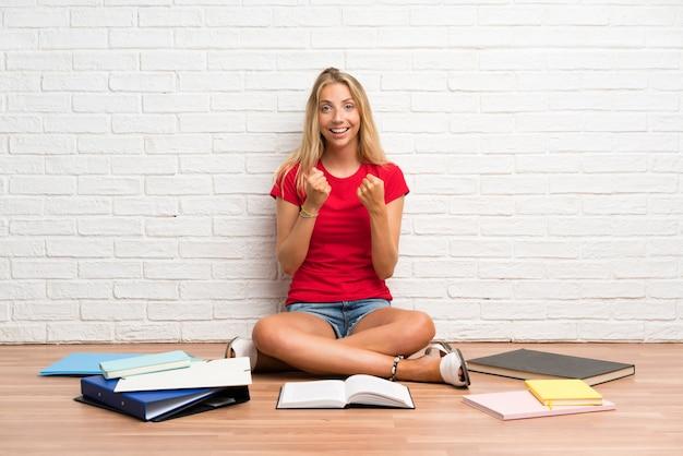 勝利を祝って床に多くの本を持つ若い金髪学生少女