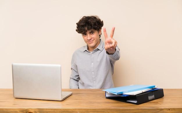 笑顔と勝利のサインを示すラップトップを持つ若い学生男
