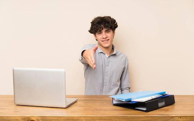 かなりを閉じるために握手するラップトップを持つ若い学生男