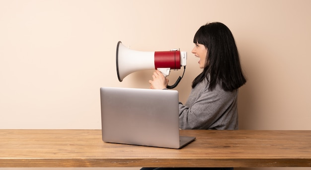 メガホンを叫んでいる彼女のラップトップで働く若い女性
