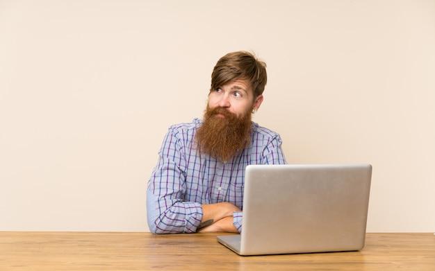 Рыжий мужчина с длинной бородой в столе с ноутбуком стоит и смотрит в сторону