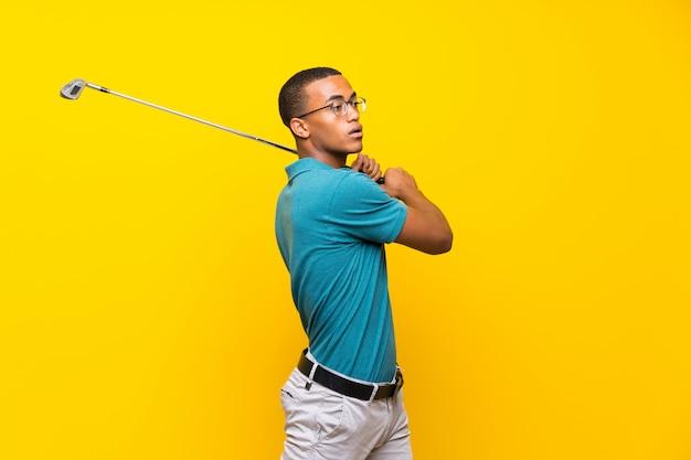 孤立した黄色の背景の上のアフロアメリカンゴルファープレーヤー男