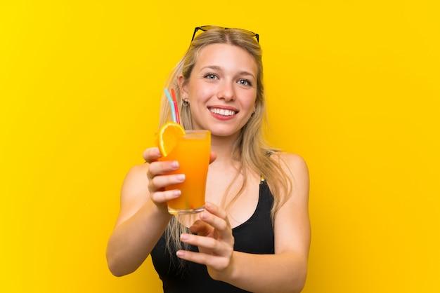 カクテルと黄色の背景の上の水着の若い女性