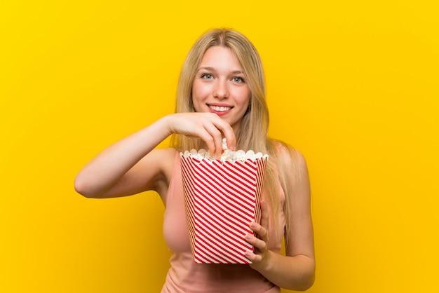 ピンクの壁の上のポップコーンを持つ若い女性