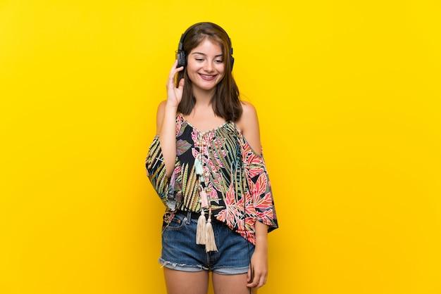 ヘッドフォンで音楽を聞いて孤立した黄色の背景にカラフルなドレスの白人少女