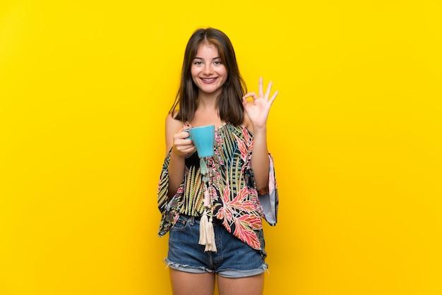 熱い一杯のコーヒーを保持している孤立した黄色の背景上のカラフルなドレスの白人少女