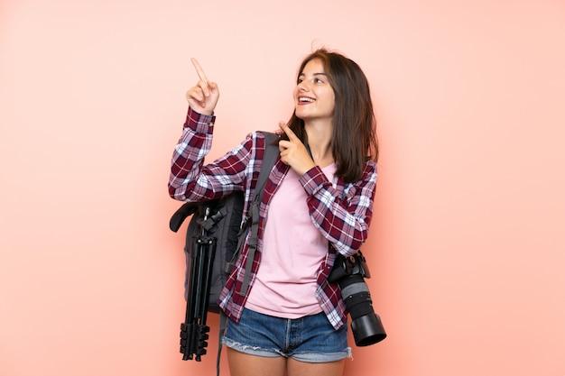 人差し指で素晴らしいアイデアを指している孤立したピンクの背景の上の若い写真家の女の子