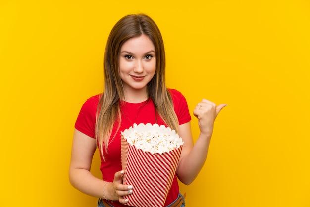 製品を提示する側を指しているピンクの壁の上のポップコーンを持つ若い女性