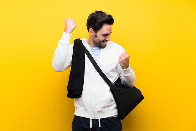 勝利を祝う孤立した黄色の壁の上の若いスポーツ男