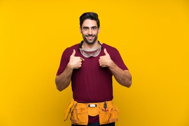 驚きの表情で孤立した黄色の背景上のハンサムな若い職人