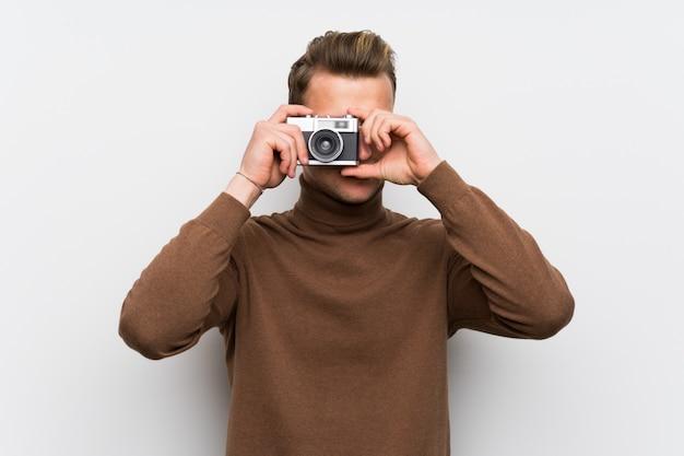 カメラを保持している孤立した白い壁に金髪の男