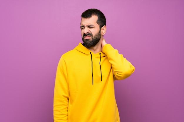 首の痛みと黄色のスウェットシャツを持つハンサムな男