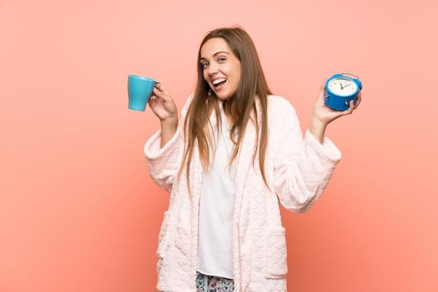 コーヒーのカップを保持しているピンクの壁の上のドレッシングガウンで幸せな若い女