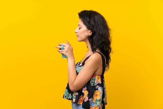 熱い一杯のコーヒーを保持している孤立した黄色の背景の上の若い女性
