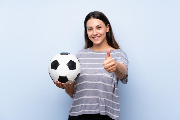 サッカーボールを保持している孤立した青い背景上の若いブルネットの女性