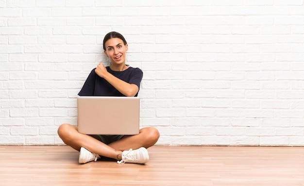 勝利を祝って床に座ってラップトップを持つ若い女性