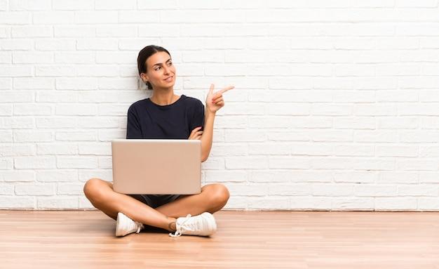 側に指を指す床に座ってラップトップを持つ若い女性