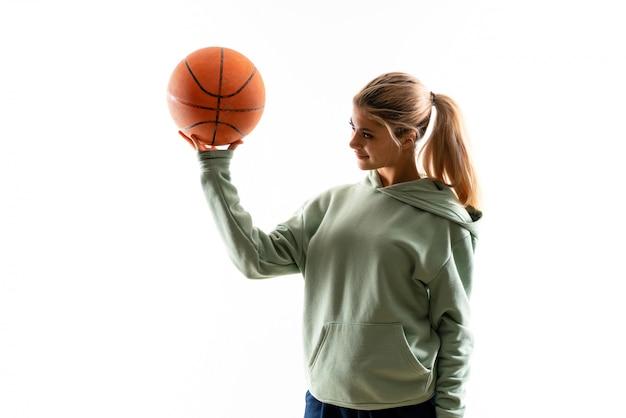 Девушка подростка играя баскетбол над изолированной белой предпосылкой