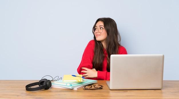 肩を持ち上げながらジェスチャーを疑ってテーブルで勉強していたティーンエイジャーの学生の女の子