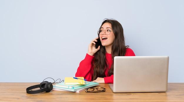 携帯電話との会話を維持するテーブルで勉強していたティーンエイジャーの学生の女の子