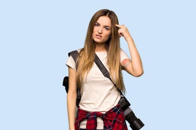 頭に指を置いて狂気のジェスチャーを作る若い写真家女性