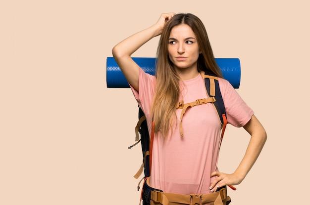 頭をかきながら疑問を持つ若いバックパッカー女性