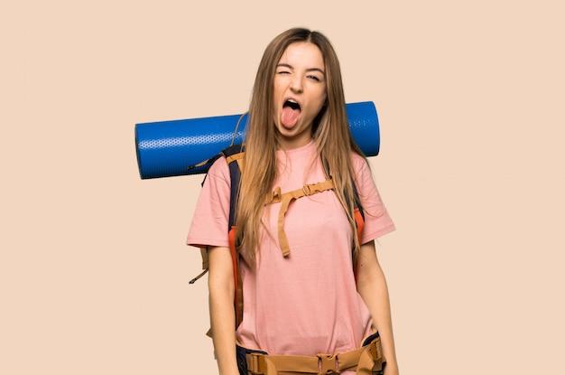 面白い表情を持つカメラで舌を示す若いバックパッカー女性