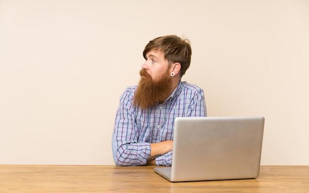 側を見ているラップトップを持つテーブルで長いひげを持つ赤毛の男
