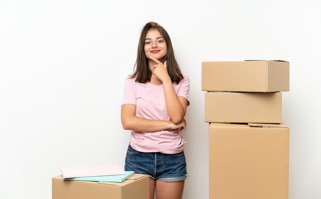 笑っているボックスの間で新しい家に移動する若い女の子