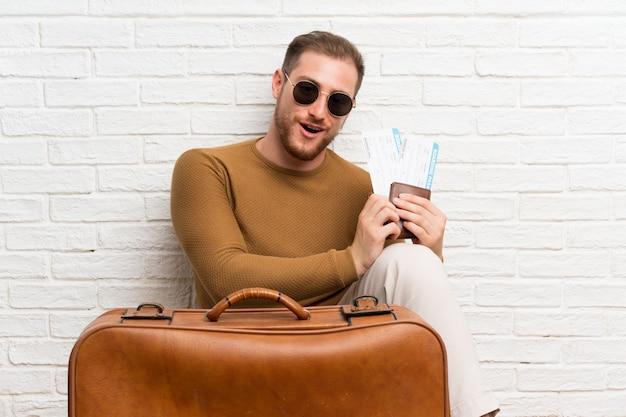 スーツケースと搭乗券を持つ旅行者男