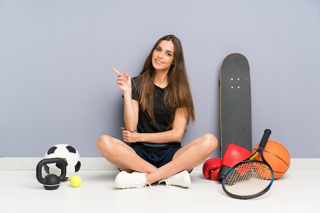 側に指を指す床に座っている若いスポーツ女性