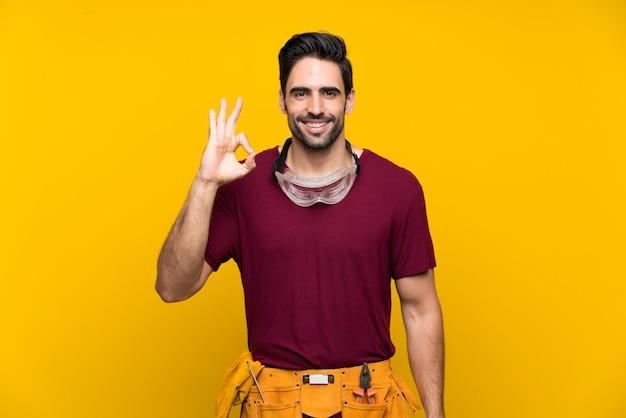 Красивый молодой мастер показывая одобренный знак с пальцами