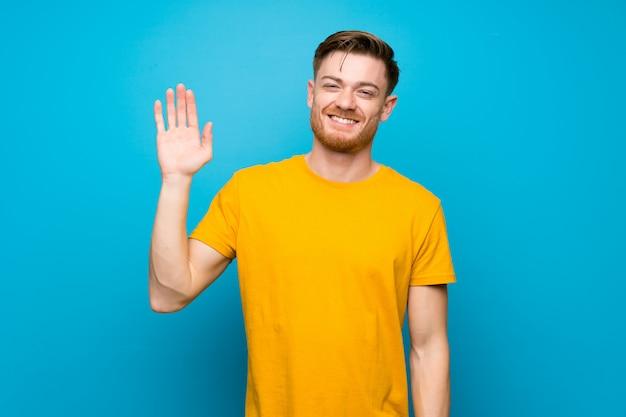 赤毛の男の幸せな表情で手で敬礼