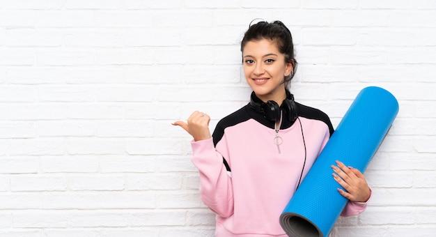 製品を提示する側を指しているマットを持つ若い女性