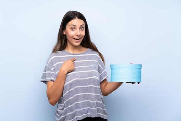 ギフト用の箱を保持している若いブルネットの女性