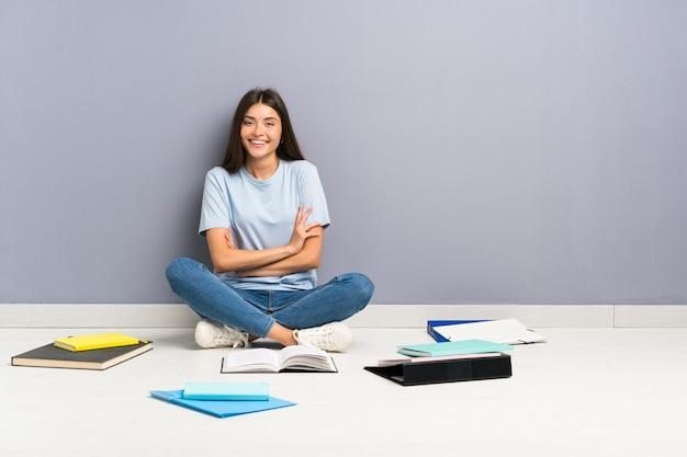 笑いながら床に多くの本を持つ若い学生女性