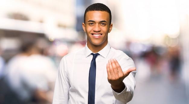 若いアフロアメリカンのビジネスマンが手に来るように招待しています。街に来てよかった