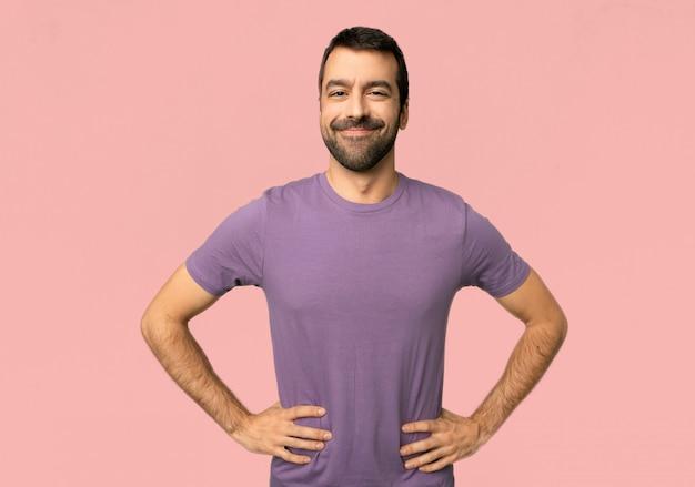 ハンサムな男の腰に腕でポーズと正面を見て笑って
