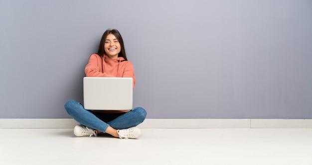 笑って床にラップトップを持つ若い学生少女