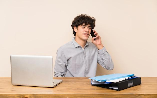 携帯電話との会話を維持するラップトップを持つ若い学生男