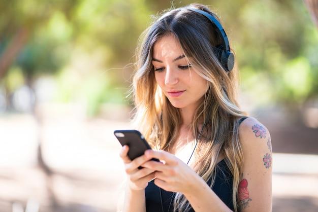 携帯電話で音楽を聴く公園で屋外で若い女の子