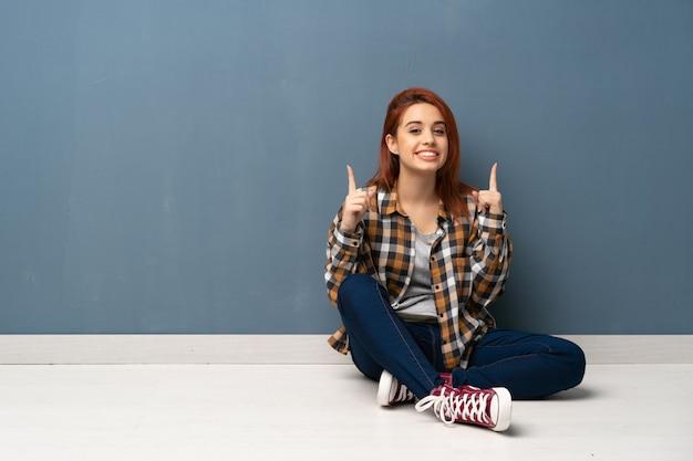 人差し指で素晴らしいアイデアを指している床に座っている若い赤毛の女性