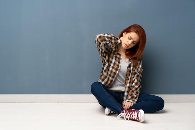 首の痛みで床に座っている若い赤毛の女性